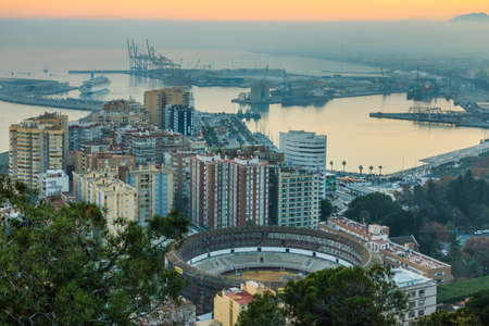 Panoramic views of the Spanish Mediterranean coast. Evening sun on the horizon from the center of the city of Malaga on the Costa del Sol with illuminated buildings, trees, street lamps, port, ships