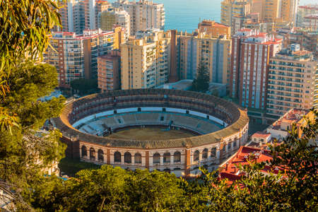 Historic bullring in Malaga from above. In the center between high-rise buildings with a view over the roofs of Malaga with sunshine and blue skies, trees and bushes