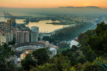 Malaga with the Spanish Mediterranean coast. Evening sun on the horizon from the center of the city on the Costa del Sol with buildings, trees, street lights, port, ships