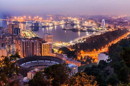 Panoramic view at night from Malaga on the Spanish Mediterranean coast. City view on the Costa del Sol with illuminated harbor, residential buildings, trees, street lamps, ferris wheel, ships