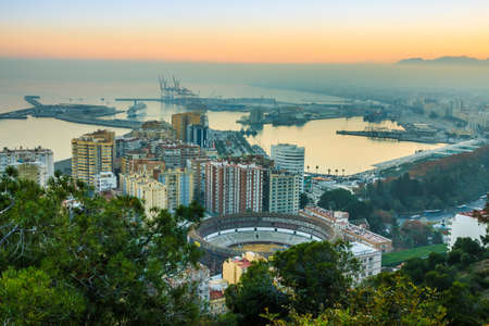 Panorama of the center of the city of Malaga. Sunset with blue sky on the Spanish Costa del Sol coastline of the city, port, houses, trees and bullring