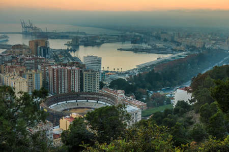 Panoramic view over from Malaga on the Spanish Mediterranean coast. View of the city center on the Costa del Sol in the evening with illuminated buildings, trees, street lamps, harbor, ships