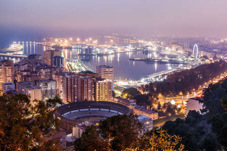 View over Malaga on the Spanish Mediterranean coast at night. Panoramic view of the city on the Costa del Sol with illuminated harbor, residential buildings, trees, street lamps, ferris wheel, ships 新聞圖片