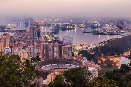 Malaga in the evening mood on the Spanish Mediterranean coast. City view on the Costa del Sol with illuminated harbor, residential buildings, trees, street lamps, ferris wheel, ships