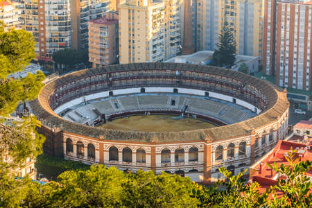 Spanish bullring on the coast in Malaga. In the middle between high-rise buildings with a view over the rooftops of Malaga with sunshine and blue sky, trees and bushes