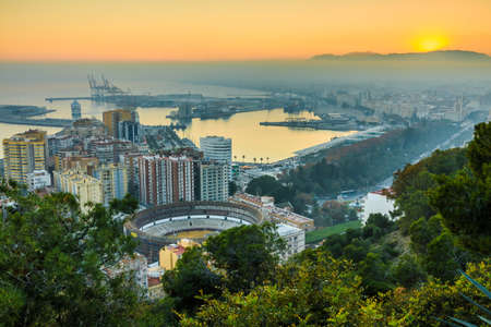 View over the center of the Spanish city of Malaga. Sunset with blue sky on the Spanish Costa del Sol of the city, the port, the houses, the trees, the bullring