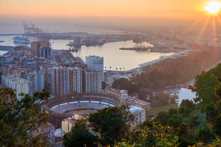 Deep sun on the horizon over Malaga. The city on the Spanish Costa del Sol at sunset with panoramic views of the harbor, houses, trees, bullring and blue sky over the mountains 新聞圖片