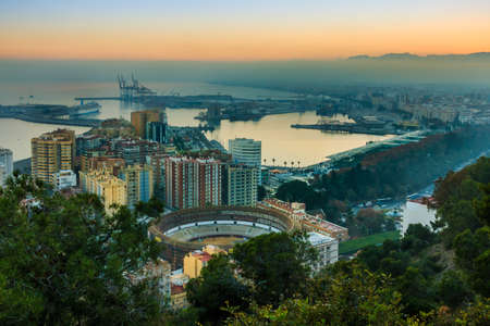 Evening sun on the Spanish Mediterranean coast. Panoramic view of the center of the city of Malaga on the Costa del Sol with illuminated buildings, trees, street lamps, port, ships 新聞圖片