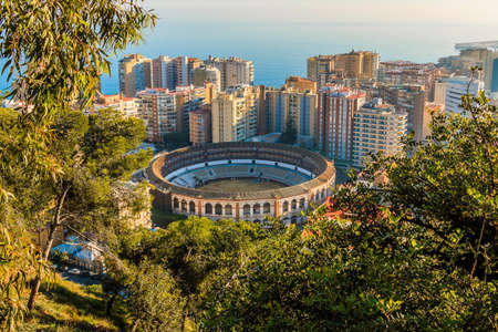 View of the bullring on the Spanish coast in Malaga. In the middle between high-rise buildings with a view over the roofs of Malaga with sunshine and blue sky, trees and bushes