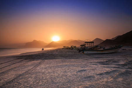 Sunset with blue and orange skies in Oman on the Dhofar and Salalah coast. Coastal area in the evening with many fishing boats and mountain ranges in the background. White sand from the beach