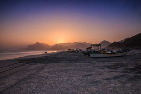 Sunset with blue and orange skies in Oman on Salalah mughsail beach. Coastal area in the evening with many fishing boats and mountain ranges in the background. White sand from the beach in the foreground 版權商用圖片