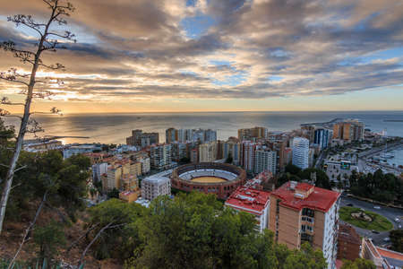 Spanish coast in Andalusia in the morning. View over the city of Malaga at sunrise with clouds and an orange horizon. City view on the Costa del Sol from park with trees and bushes