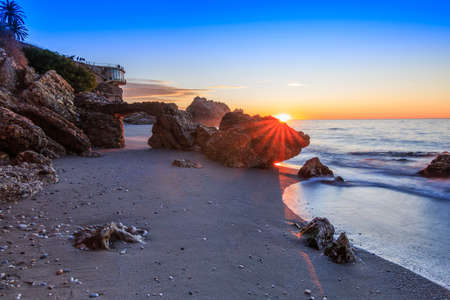 Sunrise on the Spanish coast. Balcon Europa in the city of Nerja on the Costa del Sol. Sea and rocks with arch on coastline in Andalusia. Sandy beach with sun rays and viewing platform