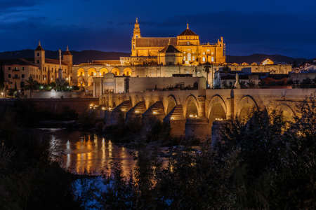 Cordoba old town in the evening at the blue hour. Mosque Cathedral with Roman bridge and river course. Illuminated buildings of the Spanish city in Andalusia