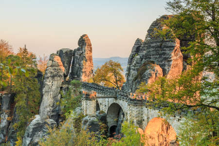 Bastei bridge in Saxon Switzerland. Historical buildings in the national park of Saxony. Rock in the evening in autumn mood. Green, brown and yellow leaves of the trees