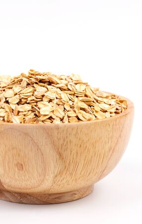avena en hojuelas: a bowl of uncooked rolled oats  on white background
