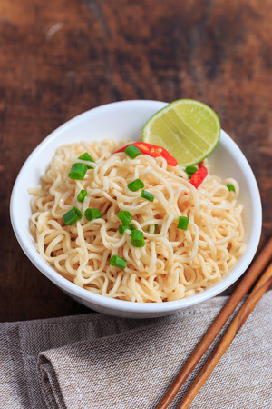 Instant noodles in white bowl on wood background.