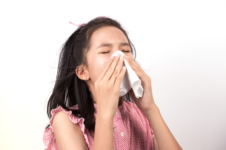Aziatisch meisje niezen met servet papier op een witte achtergrond