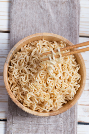 cooked instant noodle: Instant noodles in wooden bowl on wood background. Stock Photo