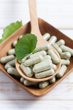 Gotu kola capsule in wooden spoon. Stock Photo