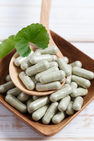 longevity drugs: Gotu kola capsule in wooden spoon. Asiatic pennywort. Stock Photo