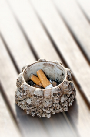 injurious: A photo of cigarette ends in an ashtray with human skulls figures