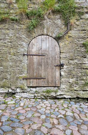 An old arch shape timber door with long metal hinges in limestone wall in Tallinn, Estonia