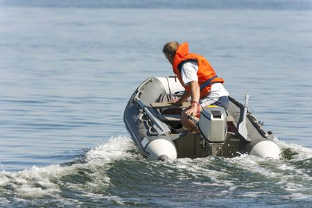 Man riding in an inflatable boat with a motor on sea