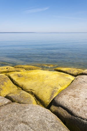 A seashore full of large limestone rocks which are partly covered with yellow algae Stock Photo - 15212642