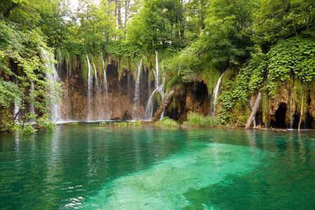 A photo of small waterfalls coming down over tussocks into the pond  The picture is taken in Plitvice, Croatia Stock Photo - 15212552