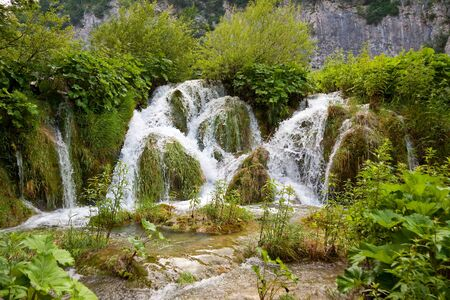 A photo of small waterfalls coming down over tussocks into the pond  The picture is taken in Plitvice, Croatia Stock Photo - 15212558