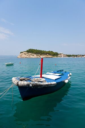 A photo of a small blue boat in water, an island in background