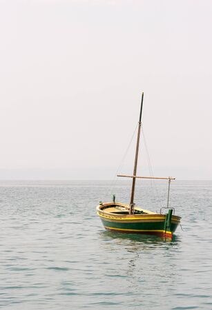 skiff: A photo of a small wooden fishing boat with a mast in water