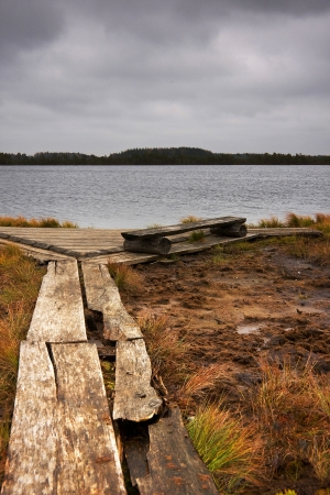 fester: Wooden road lead to a resting place with a bench and large lake in a marsh Stock Photo