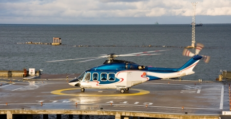 A photo of passenger helicopter waiting to take off from the platform behind fountains