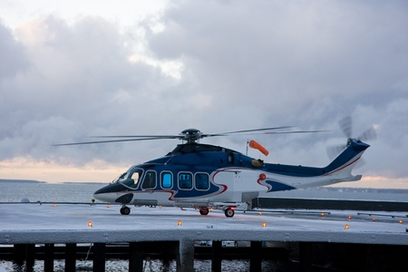 Passenger helicopter in the snow blizzard taking off from the platform