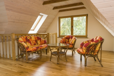 Attic room with garden furniture  Walls covered with timber planks, beams in the ceiling