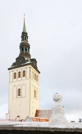 Small snowman in foreground, church St  Nicholas in Tallinn, Estonia in background
