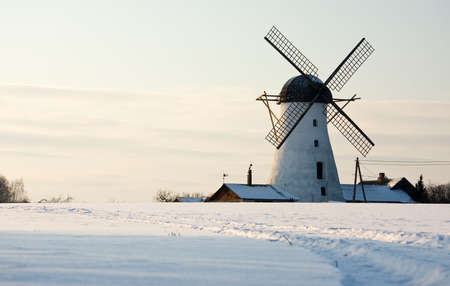 Old white windmill in Estonia at snowy winter day