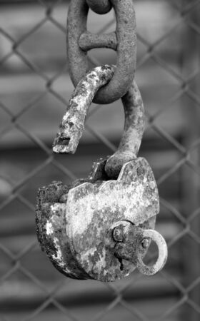 Big old rusty metal open padlock with a key hanging on a bold chain photo