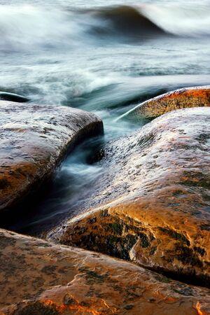 Brownish curvy stones and wavy sea  Rocks are wet and shiny  Stock Photo - 15886328