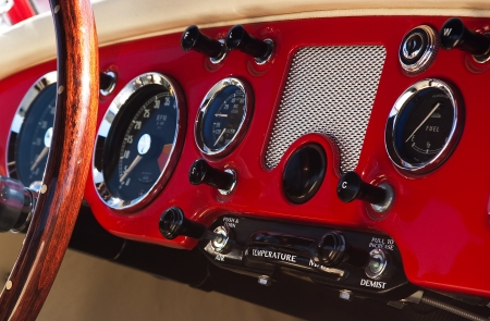 Ancient red car dashboard with a big wheel and several buttons and mechanical displays photo