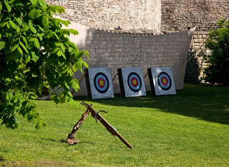Crossbow and three colorful targets in front of a big curtain wall of the Old Town of Tallinn, Estonia