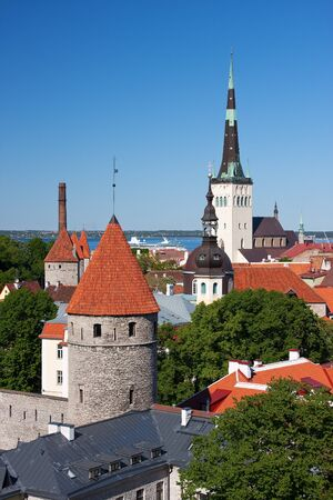 Cityscape picture taken in the Old Town of Tallinn, Estonia  Houses with red roof and church St  Olaf in bacground  photo