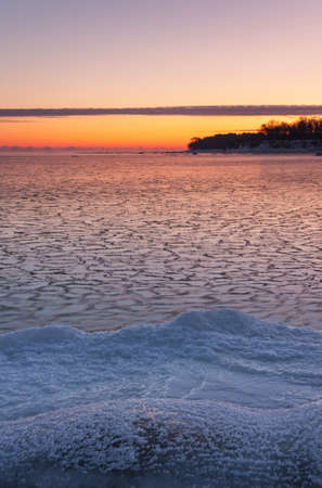 Icy sea at sunrise, snowy land in foreground and a piece of land in background Stock Photo - 16134778