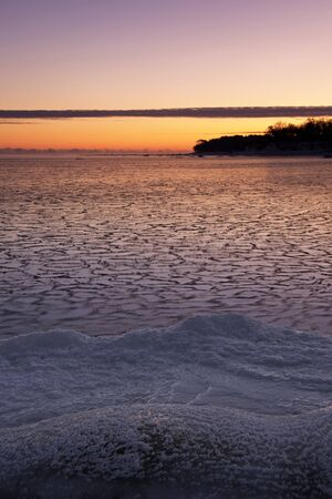 Icy sea at sunrise, snowy land in foreground and a piece of land in background Stock Photo - 16358426