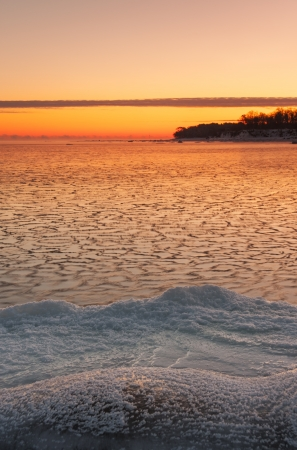 Icy sea at sunrise, snowy land in foreground and a piece of land in background Stock Photo - 16101792