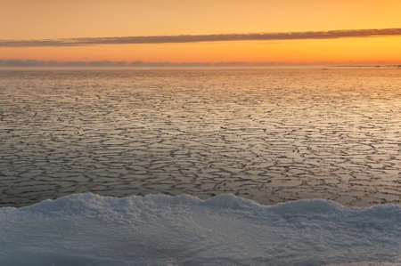 Icy sea at sunrise, snowy land in foreground Stock Photo - 16101795