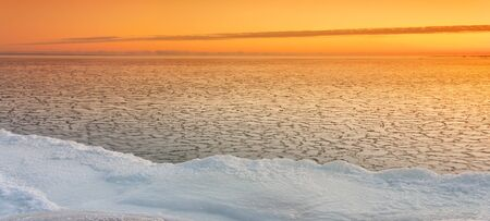 Icy sea at sunrise, snowy land in foreground Stock Photo - 16101824