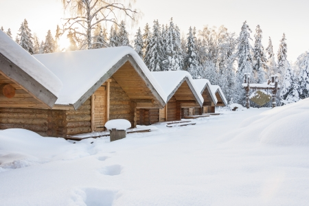 Snowy huts covered with snow at bright snowy day  Forest in background